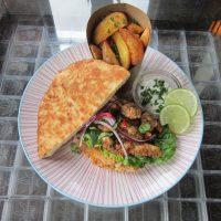 Kip Tikka geserveerd op naanbrood, romana sla , rode ui, koriander , limoen en een yoghurt -muntsaus geserveerd met aardappel wedges