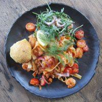 Griekse scampi's met pittige tomatensaus, feta kaas, tomaat, en dille geserveerd met tagliatelle en brood.