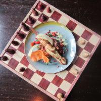 Gegrilde kip spies met avocado crème, geserveerd met een quinoa salade met pompoenpitten, gedroogde abrikoos , rozijnen, feta en een krokantje van geroosterde paprika.