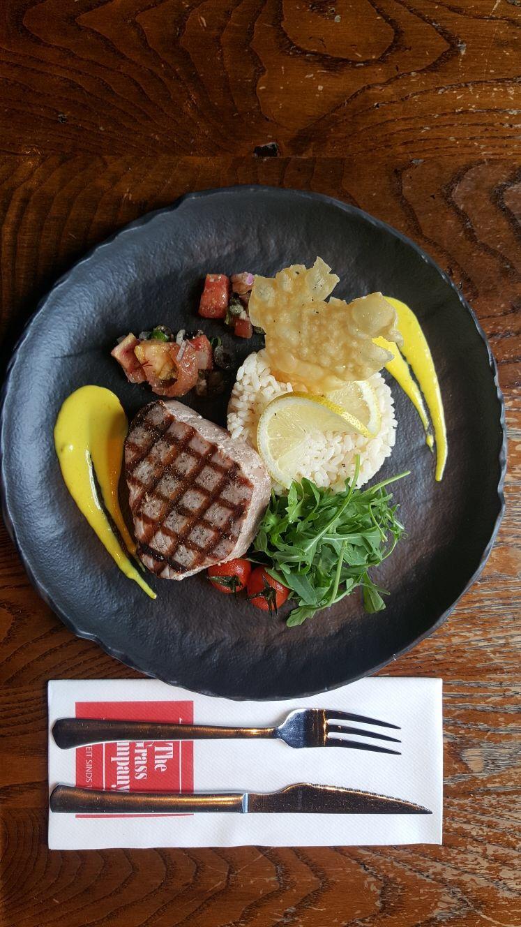 Gegrilde tonijnsteak met een tomaten-olijven salsa , citroenrisotto en een saus van saffraan.
